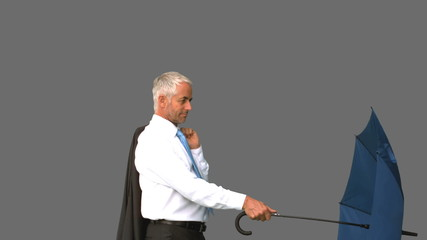 Businessman going under his umbrella on grey screen