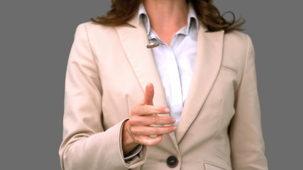 Pretty businesswoman throwing a coin on grey screen