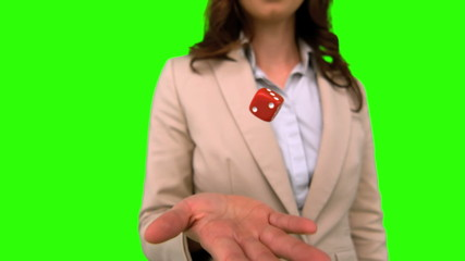 Businesswoman throwing a die on green screen