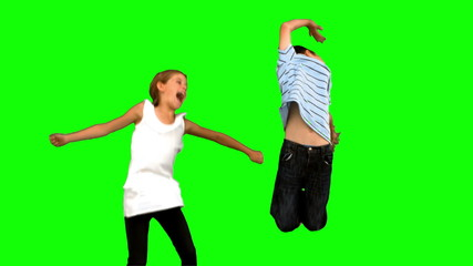 Siblings jumping together on green screen