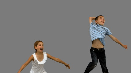Brother and sister jumping together on grey screen