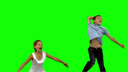 Brother and sister jumping together on green screen
