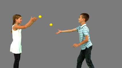 Siblings playing with tennis balls on grey screen