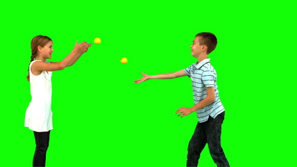 Siblings playing with tennis balls on green screen