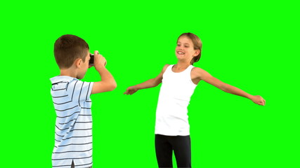 Brother taking pictures of his sister jumping on green screen