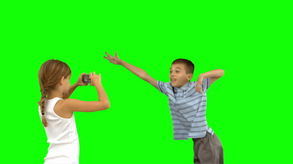 Sister taking pictures of her brother jumping on green screen