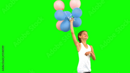 Little girl playing with balloons on green screen