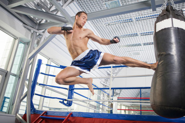 Kickboxer. Confident young kickboxer training at the punching ba