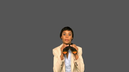 Concentrated businesswoman jumping while holding binoculars