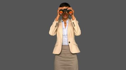 Astonished businesswoman holding binoculars