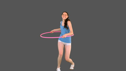 Young model in sportswear exercising with hula hoop