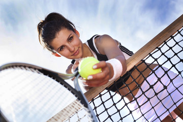 Beautiful young girl rests on a tennis net