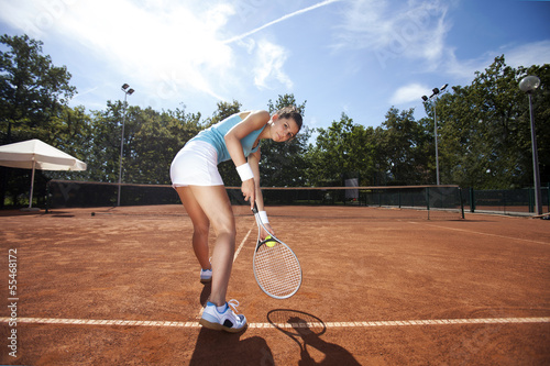 Young girl playing tennis at the beautiful weather