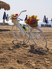 bicycle parked on a beach next to the umbrellas