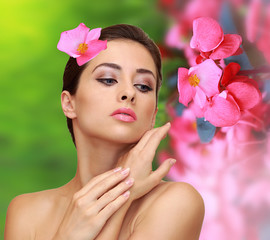 Beautiful woman with pink flowers. Beauty model perfect skin fac