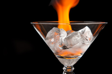Ice cubes in glass with flame on shiny black surface