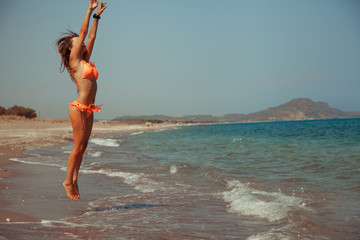 woman jumping on the beach in bikini