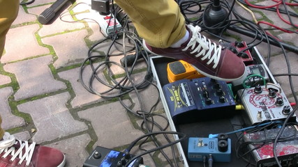 Guitarist pushing pedal effects during live concert
