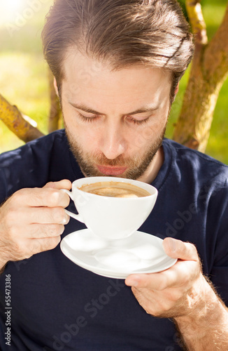 Caucasian man drinking morning coffee outdoor in the garden