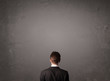 Businessman standing in front of an empty wall