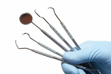 Hand with professional dental tools.