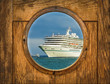 Ship porthole window with seascape and cruise ship