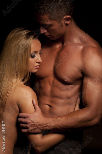 Young and fit topless couple in an embrace on dark background