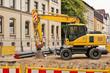 Ein gelber Bagger vor einem älteren Haus beim Strassenbau