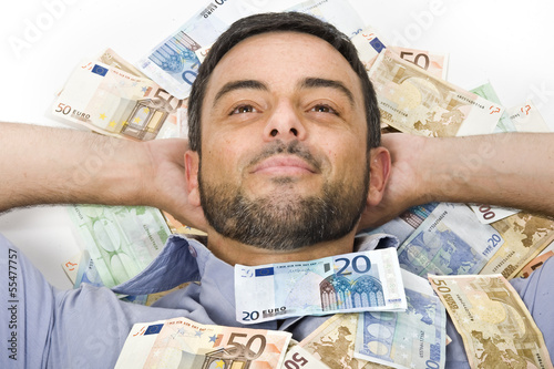 Happy Young Man laying on Banknotes