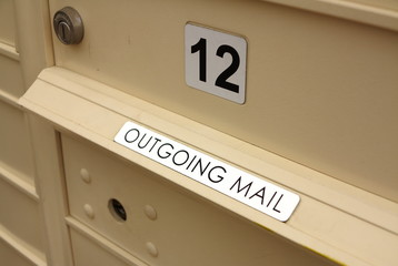 Close up of outgoing mail slot and lockable metal mailbox