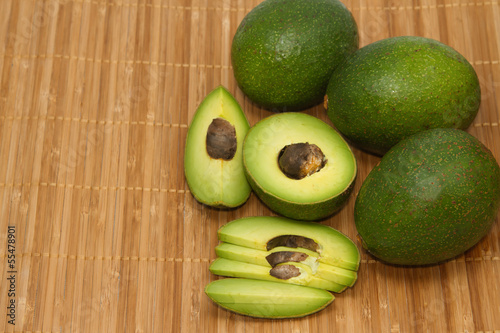 fresh avocado fruits on wooden background