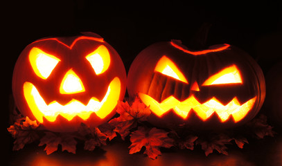 Spooky Halloween Jack o Lanterns with leaves at night