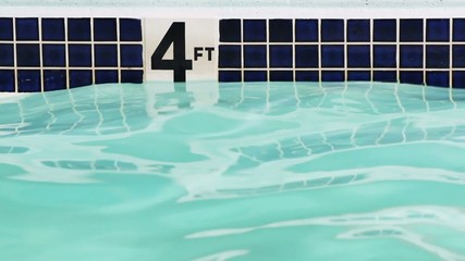 Four foot depth marker on side of swimming pool