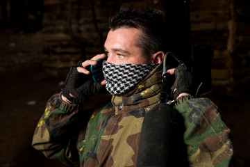 Paintball player calling someone at the phone