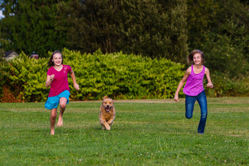 Two girls running with a dog