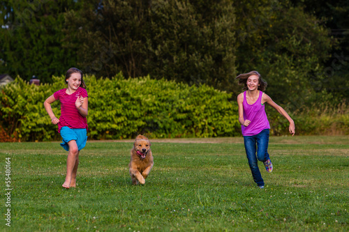 two kids running with a dog