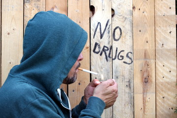"""Zigarettensüchtiger """"auf Holzwand steht """"no drugs"""""""