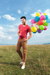 casual man with baloons over his shoulder