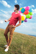 casual man with baloons looks back
