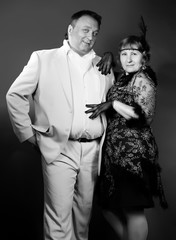 Mid aged plus size couple posing in retro style over dark backgr