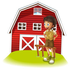 A boy standing in front of the red barnhouse