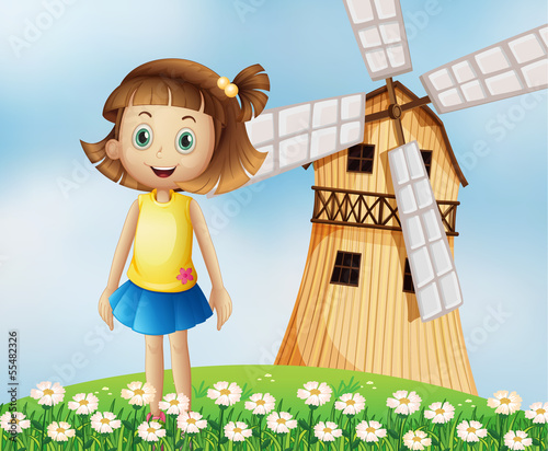 A young girl at the top of the hill with a windmill