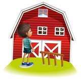 A boy standing in front of the red farmhouse