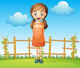 A little woman standing near the wooden fence