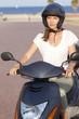 Attraktive Frau auf einem Roller