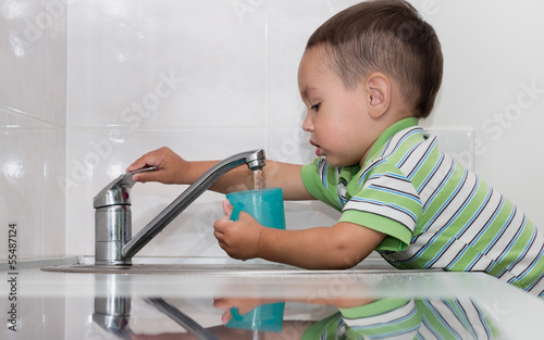 Little boy washing dishes