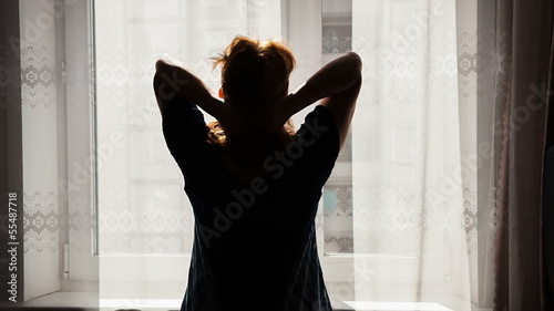 Woman wakes up, Silhouette of the woman against window