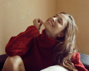 young woman in sweater at home smiling