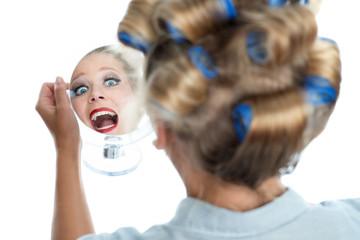 Frau mit Lockenwicklern schaut in den Spiegel