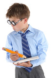 Schoolboy wearing glasses holding book and pencil and looking si